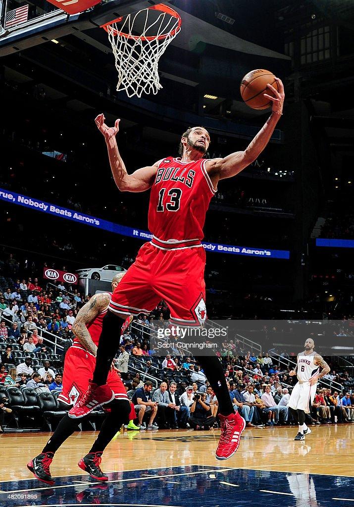 Joakim Noah #13 of the Chicago Bulls grabs a rebound against the Atlanta Hawks on April 2, 2014 at Philips Arena in Atlanta, Georgia.