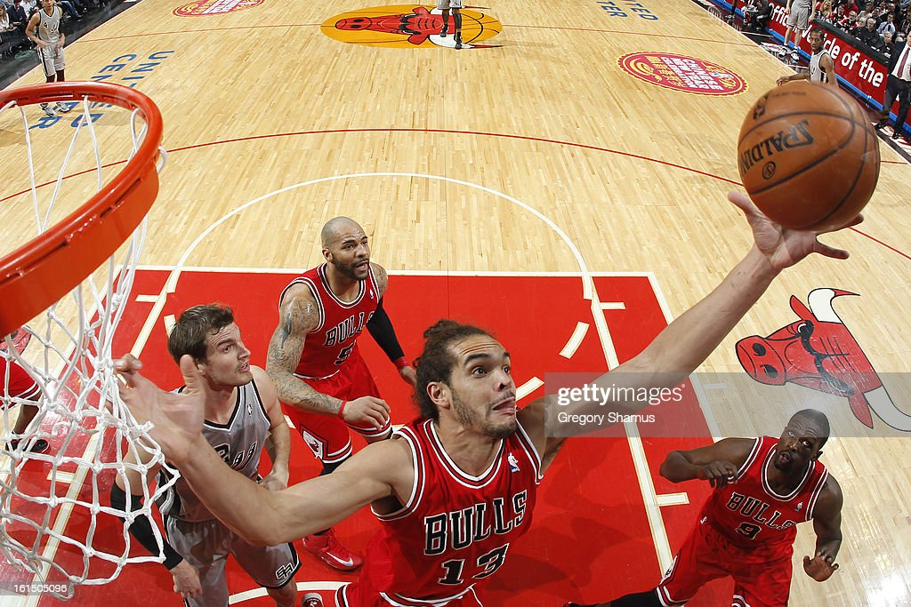 Joakim Noah #13 of the Chicago Bulls grabs a rebound against the San Antonio Spurs on February 11, 2013 at the United Center in Chicago, Illinois.