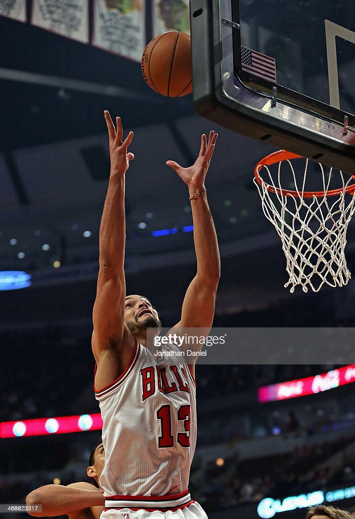 Joakim Noah #13 of the Chicago Bulls grabs one of 16 rebounds against the Atlanta Hawks at the United Center on February 11, 2014 in Chicago, Illinois.