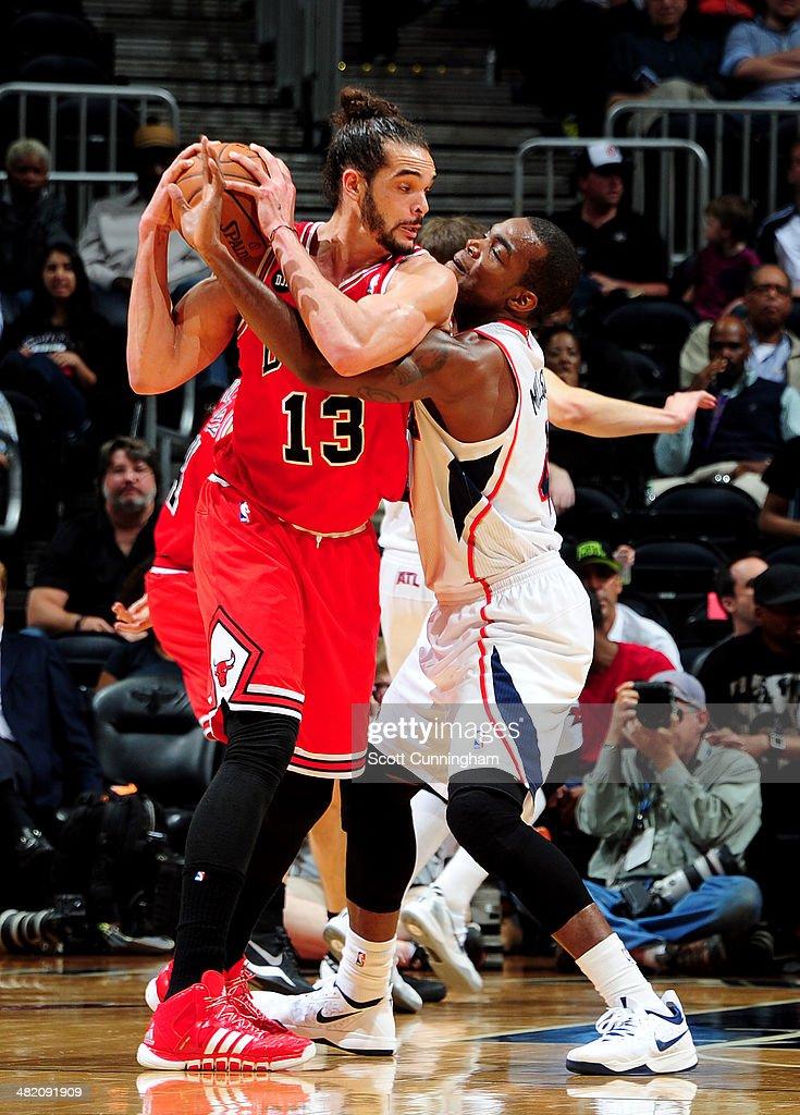 Joakim Noah #13 of the Chicago Bulls handles the ball against Paul Millsap #4 of the Atlanta Hawks on April 2, 2014 at Philips Arena in Atlanta, Georgia.