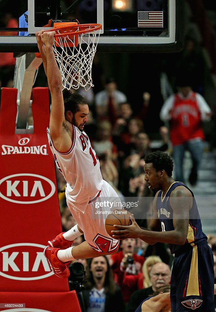 Joakim Noah #13 of the Chicago Bulls hangs on the rim after dunking over Al-Farouq Aminu #0 of the New Orleans Pelicans at the United Center on December 2, 2013 in Chicago, Illinois. The Pelicans defeated the Bulls 131-128 in triple overtime.
