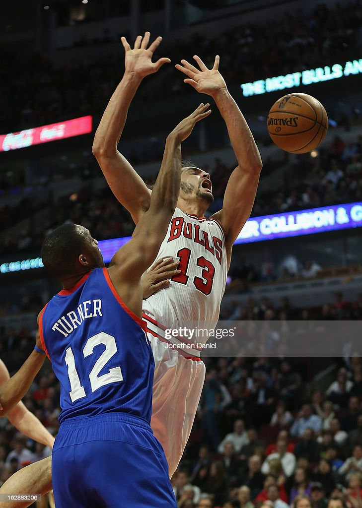 Joakim Noah #13 of the Chicago Bulls is fouled by Evan Turner #12 of the Phildelphia 76ers as he goes up to shoot at the United Center on February 28, 2013 in Chicago, Illinois. The Bulls defeated the 76ers 93-82.