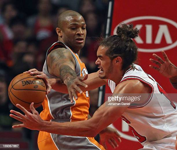 Joakim Noah of the Chicago Bulls is fouled while rebounding by PJ Tucker of the Phoenix Suns at the United Center on January 12 2013 in Chicago...