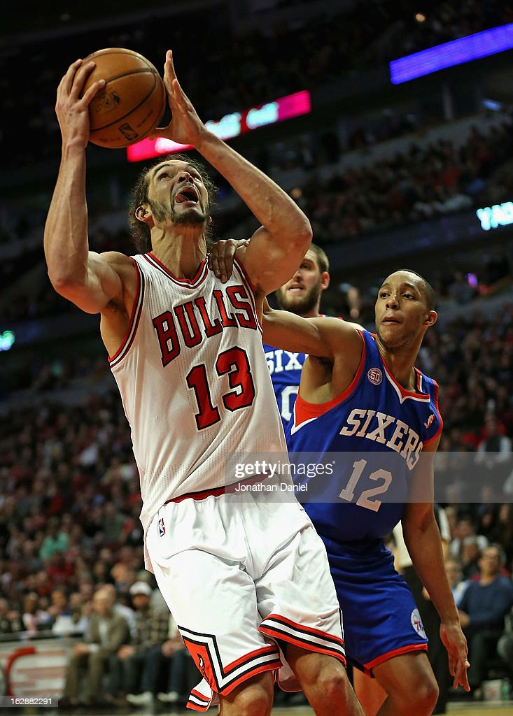 Joakim Noah #13 of the Chicago Bulls is grabbed by Evan Turner #12 of the Phildelphia 76ers as he goes up to shoot at the United Center on February 28, 2013 in Chicago, Illinois. The Bulls defeated the 76ers 93-82.