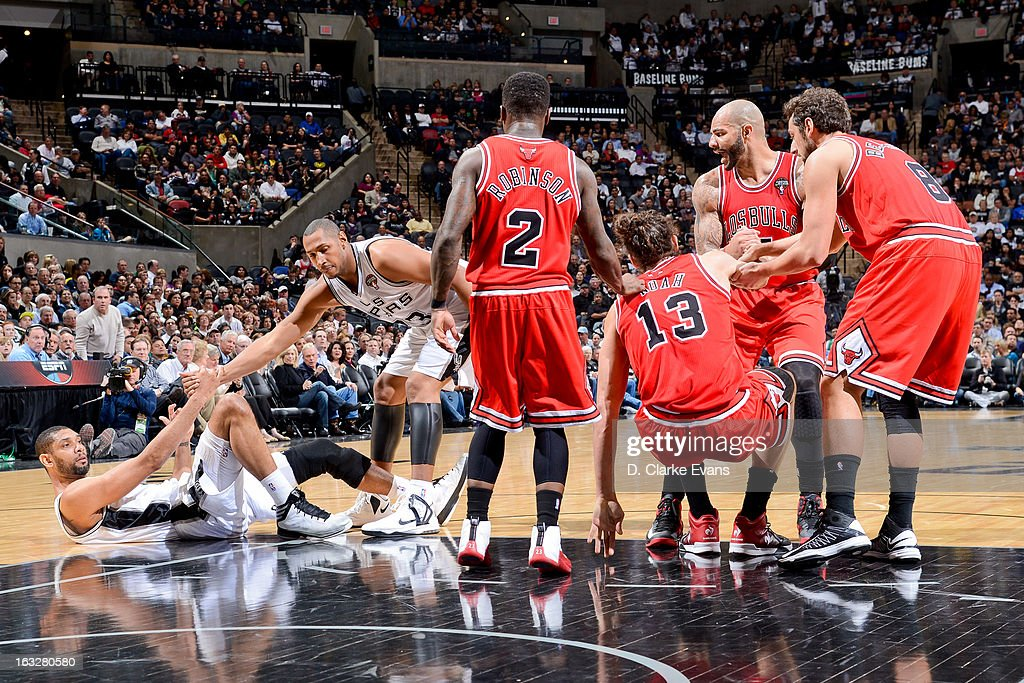 Joakim Noah #13 of the Chicago Bulls is helped up by teammates Nate Robinson #2, Marco Belinelli #8 and Carlos Boozer #5 as Tim Duncan #21 of the San Antonio Spurs is helped up by teammate Boris Diaw #33 during their game on March 6, 2013 at the AT&T Center in San Antonio, Texas.
