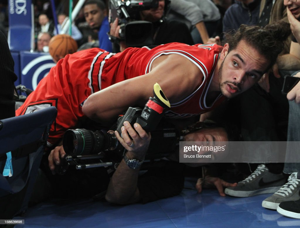 <a gi-track='captionPersonalityLinkClicked' href=/galleries/search?phrase=Joakim+Noah&family=editorial&specificpeople=699038 ng-click='$event.stopPropagation()'>Joakim Noah</a> #13 of the Chicago Bulls lands on a TV camerman during the second quarter against the New York Knicks at Madison Square Garden on December 21, 2012 in New York City.