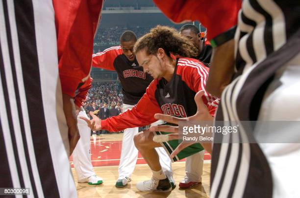 Joakim Noah of the Chicago Bulls leads the team in their pregame ritual huddle following introductions for the game against the New Jersey Nets on...