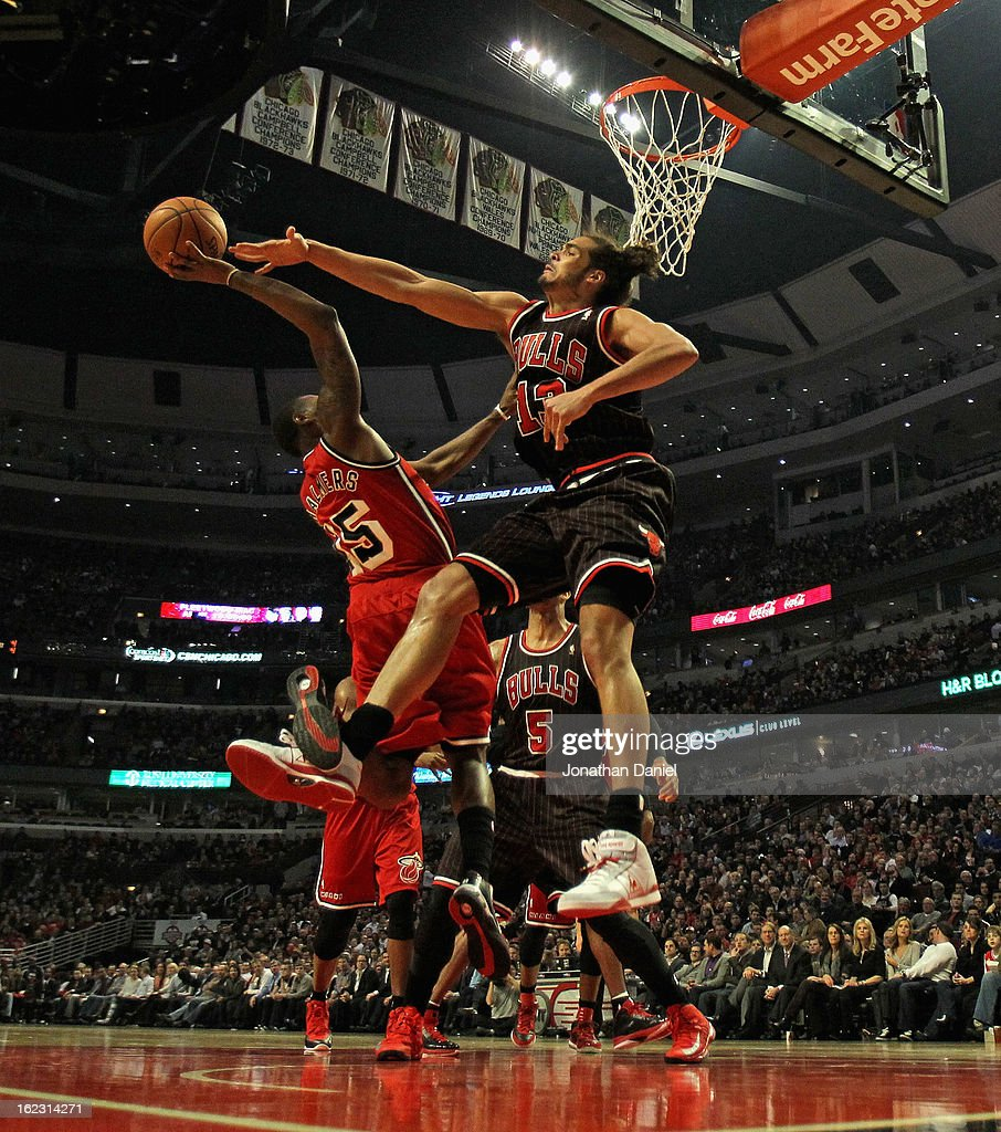 Joakim Noah #13 of the Chicago Bulls leaps to conterst a shot by Mario Chalmers #15 of the Miami Heat at the United Center on February 21, 2013 in Chicago, Illinois.