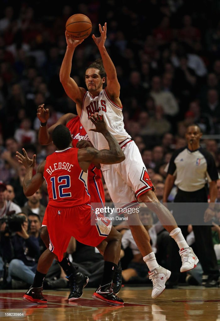 Joakim Noah #13 of the Chicago Bulls passes over Eric Bledsoe #12 of the Los Angeles Clippers at the United Center on December 11, 2012 in Chicago, Illinois.