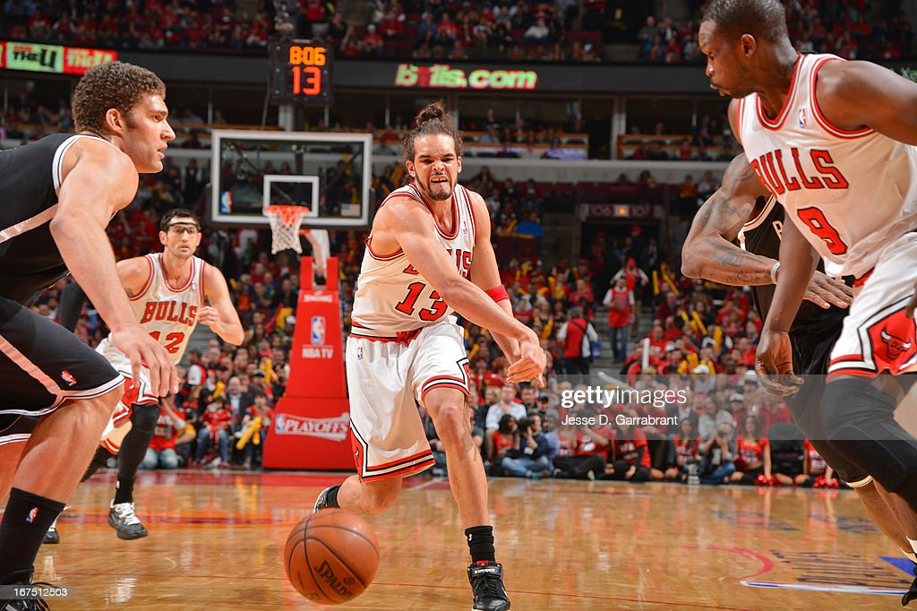 Joakim Noah #13 of the Chicago Bulls passes the ball to teammate Luol Deng #9 who cuts in front of Brook Lopez #11 of the Brooklyn Nets in Game Three of the Eastern Conference Quarterfinals during the 2013 NBA Playoffs on April 25, 2013 at United Center in Chicago, Illinois.