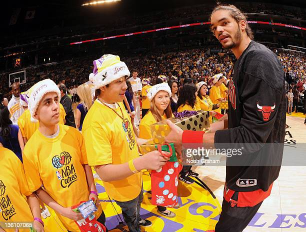 Joakim Noah of the Chicago Bulls presents gifts to fans at center court before the game against the Los Angeles Lakers at Staples Center on December...