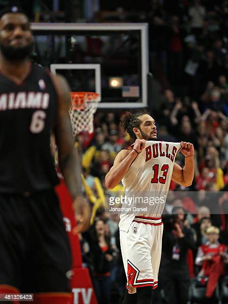 Joakim Noah of the Chicago Bulls pulls on his jersey in celebration as LeBron James of the Miami Heat walks down the court at the United Center on...