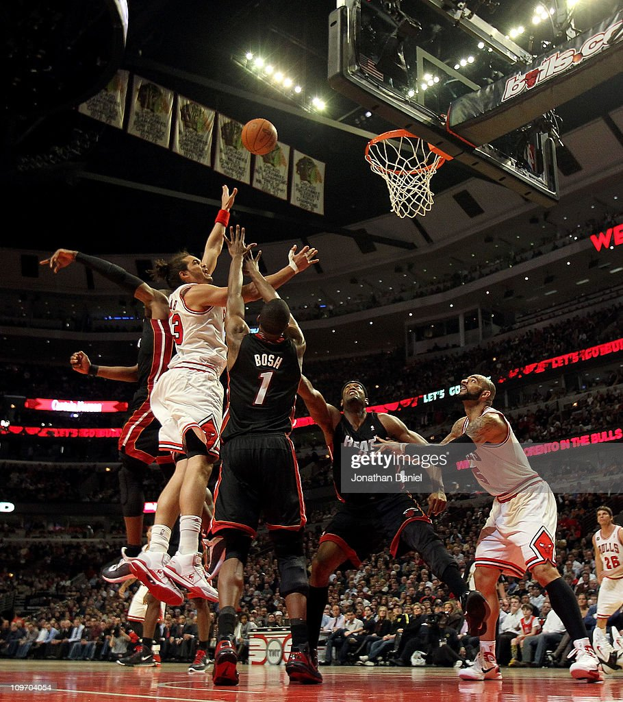 <a gi-track='captionPersonalityLinkClicked' href=/galleries/search?phrase=Joakim+Noah&family=editorial&specificpeople=699038 ng-click='$event.stopPropagation()'>Joakim Noah</a> #13 of the Chicago Bulls puts up a shot between <a gi-track='captionPersonalityLinkClicked' href=/galleries/search?phrase=Chris+Bosh&family=editorial&specificpeople=201574 ng-click='$event.stopPropagation()'>Chris Bosh</a> #1 and <a gi-track='captionPersonalityLinkClicked' href=/galleries/search?phrase=Dwyane+Wade&family=editorial&specificpeople=201481 ng-click='$event.stopPropagation()'>Dwyane Wade</a> #3 of the Miami Heat at the United Center on February 24, 2011 in Chicago, Illinois. The Bulls defeated the Heat 93-89.