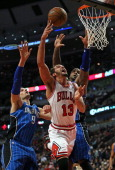 Joakim Noah of the Chicago Bulls puts up a shot between Nikola Vucevic and Glen Davis of the Orlando Magic at the United Center on December 16 2013...