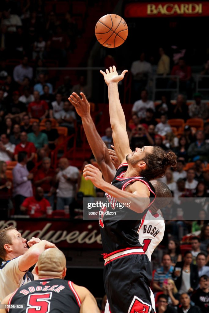Joakim Noah #13 of the Chicago Bulls reaches for the opening tip-off against Chris Bosh #1 of the Miami Heat on January 4, 2013 at American Airlines Arena in Miami, Florida.