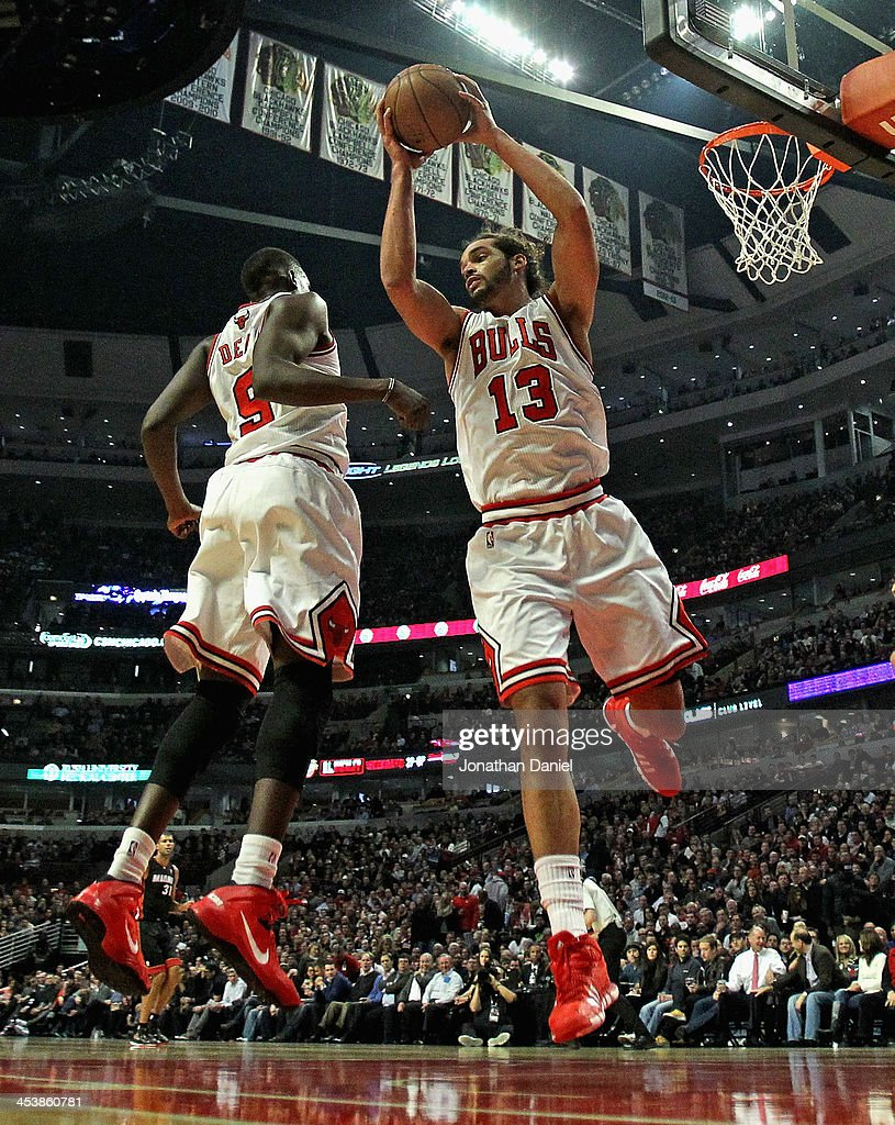 Joakim Noah #13 of the Chicago Bulls rebounds over teammate Loul Deng #9 against the Miami Heat at the United Center on December 5, 2013 in Chicago, Illinois.