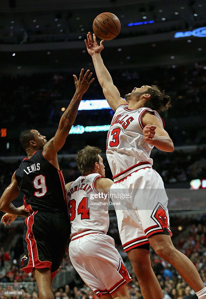 Joakim Noah #13 of the Chicago Bulls rebounds over teammate Mike Dunleavy #34 and Rashard Lewis #9 of the Miami Heat at the United Center on December 5, 2013 in Chicago, Illinois.