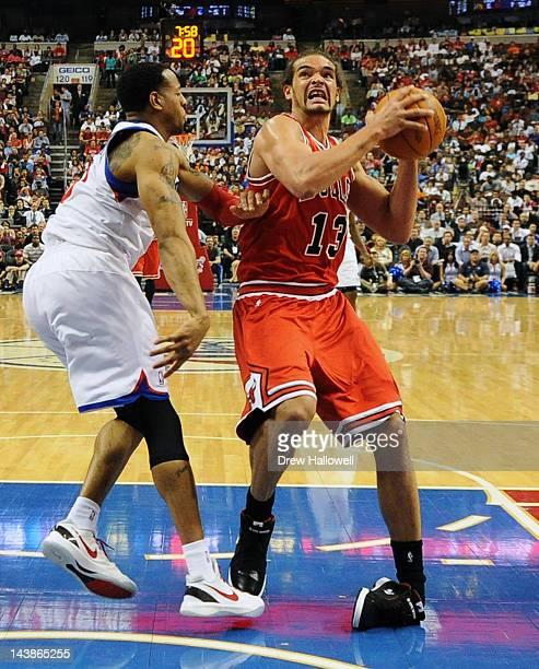 Joakim Noah of the Chicago Bulls rolls his ankle while driving to the basket against Andre Iguodala of the Philadelphia 76ers in Game Three of the...