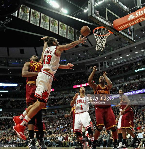 Joakim Noah of the Chicago Bulls shoots around Andrew Bynum of the Cleveland Cavaliers at the United Center on November 11 2013 in Chicago Illinois...