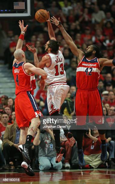 Joakim Noah of the Chicago Bulls shoots between Marcin Gortat and Nene of the Washington Wizards in Game Two of the Eastern Conference Quarterfinals...