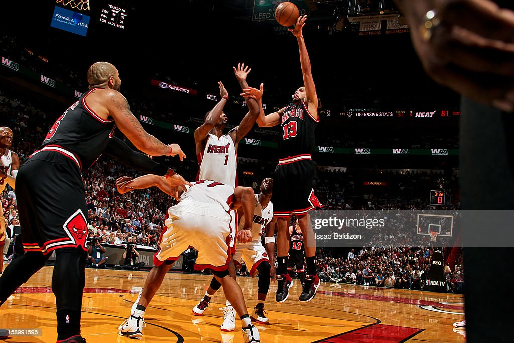 <a gi-track='captionPersonalityLinkClicked' href=/galleries/search?phrase=Joakim+Noah&family=editorial&specificpeople=699038 ng-click='$event.stopPropagation()'>Joakim Noah</a> #13 of the Chicago Bulls shoots in the lane against <a gi-track='captionPersonalityLinkClicked' href=/galleries/search?phrase=Chris+Bosh&family=editorial&specificpeople=201574 ng-click='$event.stopPropagation()'>Chris Bosh</a> #1 of the Miami Heat on January 4, 2013 at American Airlines Arena in Miami, Florida.