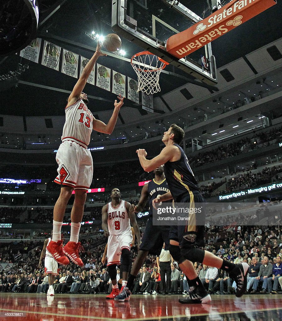 Joakim Noah #13 of the Chicago Bulls shoots over Jason Smith #14 of the New Orleans Pelicans at the United Center on December 2, 2013 in Chicago, Illinois. The Pelicans defeated the Bulls 131-128 in triple overtime.