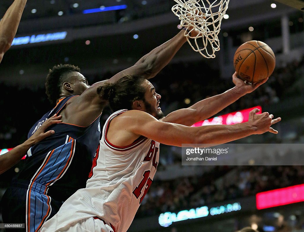 Joakim Noah #13 of the Chicago Bulls shoots under pressure from Jeff Adrien #4 of the Charlotte Bobcats at the United Center on November 18, 2013 in Chicago, Illinois. The Bulls defeated the Bobcats 86-81.