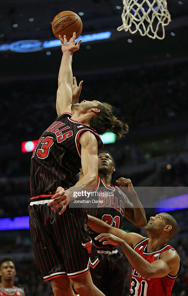 Joakim Noah #13 of the Chicago Bulls tries for a rebound over teammate Jimmy Butler #21 and Shane Battier #31 of the Miami Heat at the United Center on February 21, 2013 in Chicago, Illinois.
