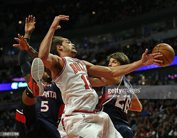 Joakim Noah of the Chicago Bulls tries to control the ball between Josh Smith and Kyle Korver of the Atlanta Hawks at the United Center on January 14...