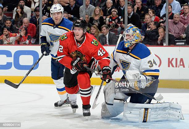Joakim Nordstrom of the Chicago Blackhawks and Ian Cole of the St Louis Blues stand in position in front of goalie Jake Allen during the NHL game at...