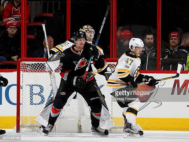 Joakim Nordstrom#42 of the Carolina Hurricanes creates traffic in front of Zane McIntyre of the Boston Bruins as Torey Krug defends during an NHL...