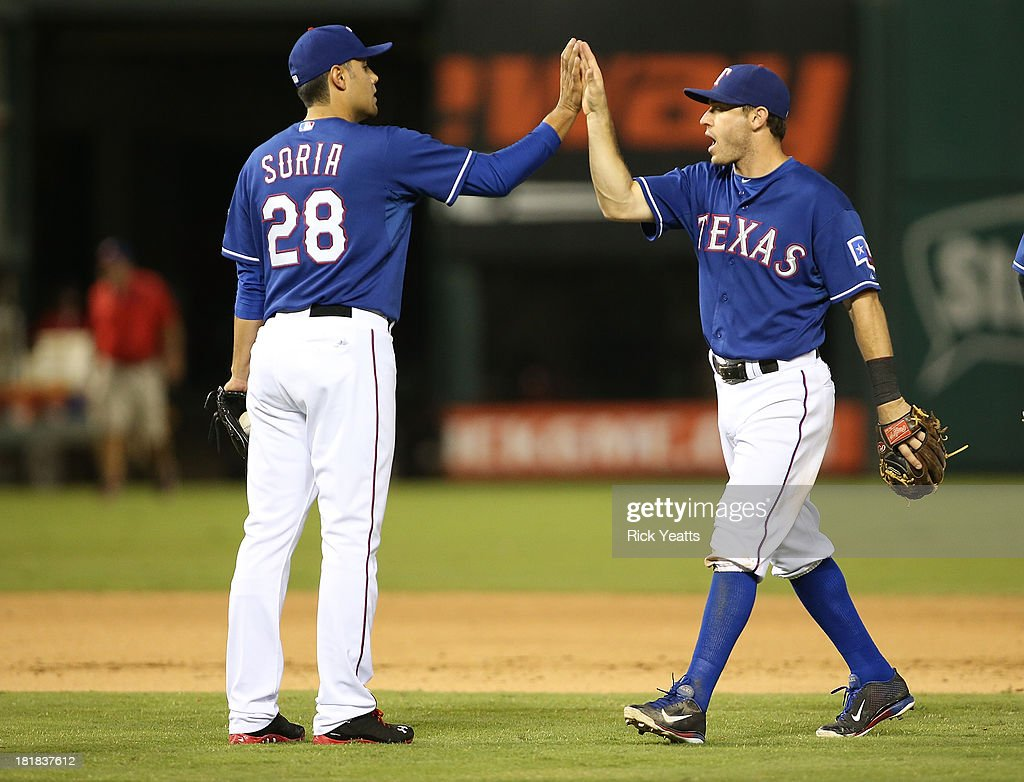 Joakim Soria #28 of the Texas Rangers is congratulated by Ian Kinsler #5 for closing out the ninth inning for the win against the Houston Astros at Rangers Ballpark in Arlington on September 25, 2013 in Arlington, Texas.