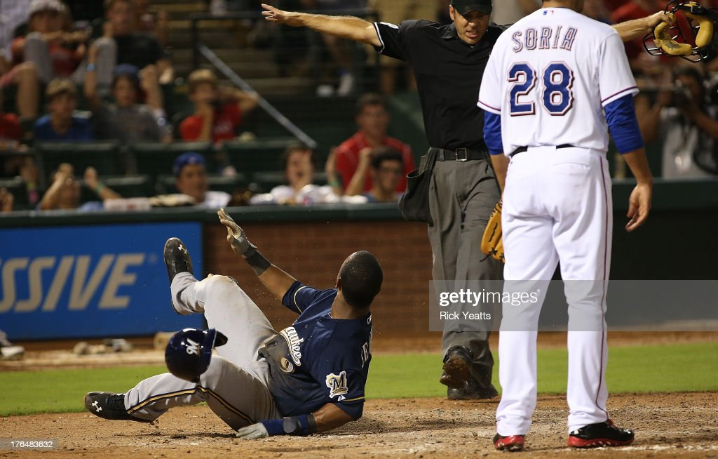 Joakim Soria of the Texas Rangers looks on as Jean Segura of the Milwaukee Brewers looks for the call by umpire James Hoye after stealing home in the...