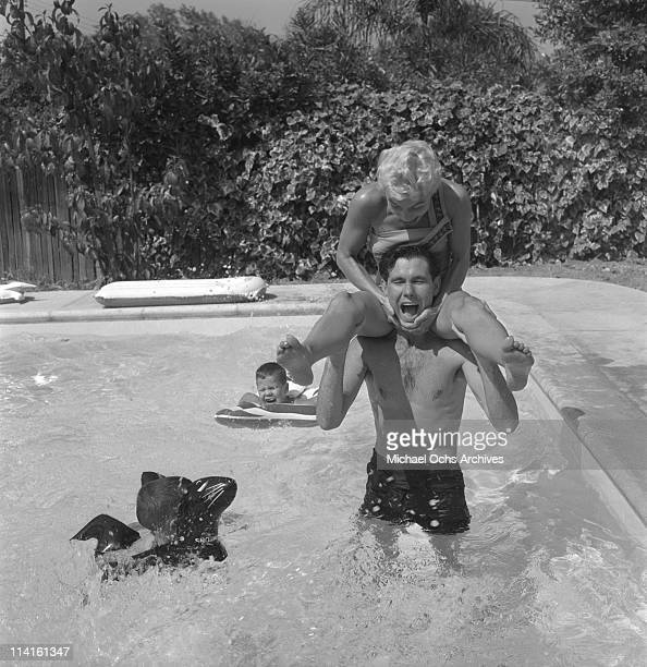 Joan and Johnny Carson host of The Johnny Carson Show on CBS frolic in their pool with two of their three sons on July 5 1956 in Los Angeles...