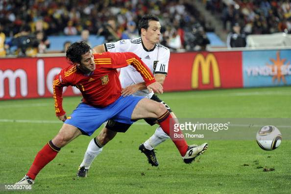 Joan Capdevila of Spain tackled by Piotr Trochowski of Germany during the 2010 FIFA World Cup South Africa Semi Final match between Germany and Spain...