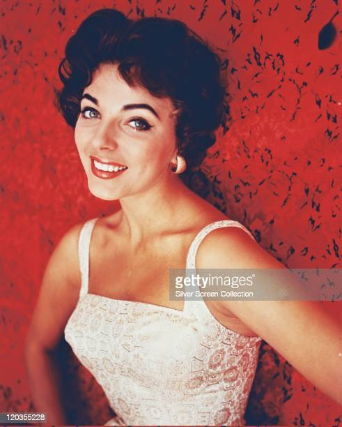 Joan Collins British actress wearing a white sleeveless top smiling in a studio portrait against a red background circa 1965
