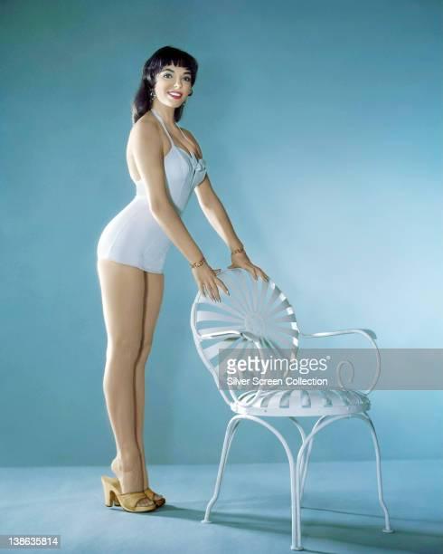 Joan Collins British actress wearing a white swimsuit leaning against the back of a white chair in a studio portrait against a light blue background...
