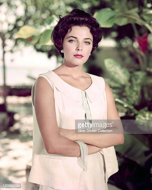 Joan Collins British actress wearing a white waistcoat with her arms folded while standing in a garden circa 1960