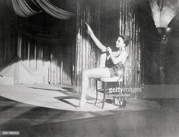 Joan Collins in a movie still from the film 'Seven Thieves' with her performing a strip tease 1960
