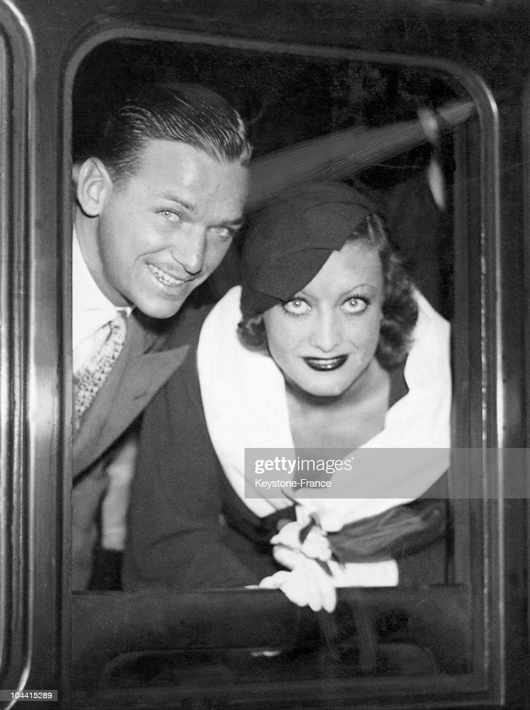 Joan CRAWFORD and Douglas FAIRBANKS junior looking out of their carriage window, prior to departure from Victoria station in London to Paris on July the 28th 1932.