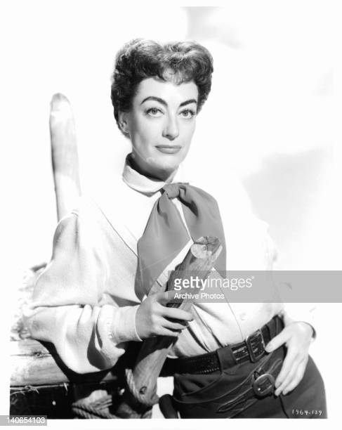 Joan Crawford leaning against wooden structure in a scene from the film 'Johnny Guitar' 1954