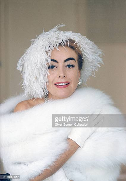 Joan Crawford US actress wearing white ostrich feather hat posing with a white fur wrap circa 1960