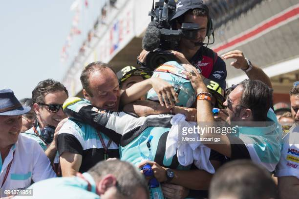 Joan Mir of Spain and Leopard Racing celebrates the victory with team under the podium at the end of the Moto3 race during the MotoGp of Catalunya...