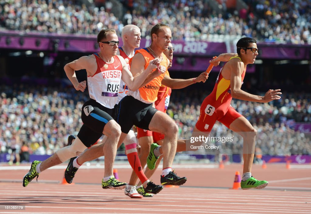 Joan Munar Martinez of Spain (5) and Andrey Koptev of Russia (7) and his guide compete in the last leg of their Men's 4x100m relay T11/13 heat on day 7 of the London 2012 Paralympic Games at Olympic Stadium on September 5, 2012 in London, England.