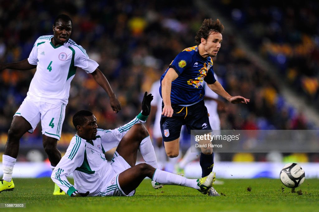 Joan Verdu (R) of Catalonia duels for the ball with Egwuekwe Azubuike of Nigeria during a friendly match between Catalonia and Nigeria at Cornella-El Prat Stadium on January 2, 2013 in Barcelona, Spain.