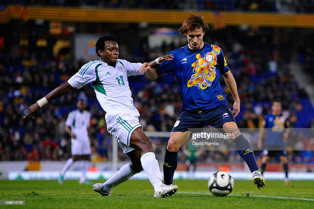 Joan Verdu (R) of Catalonia duels for the ball with Emenike Emmanuel of Nigeria during a friendly match between Catalonia and Nigeria at Cornella-El Prat Stadium on January 2, 2013 in Barcelona, Spain.