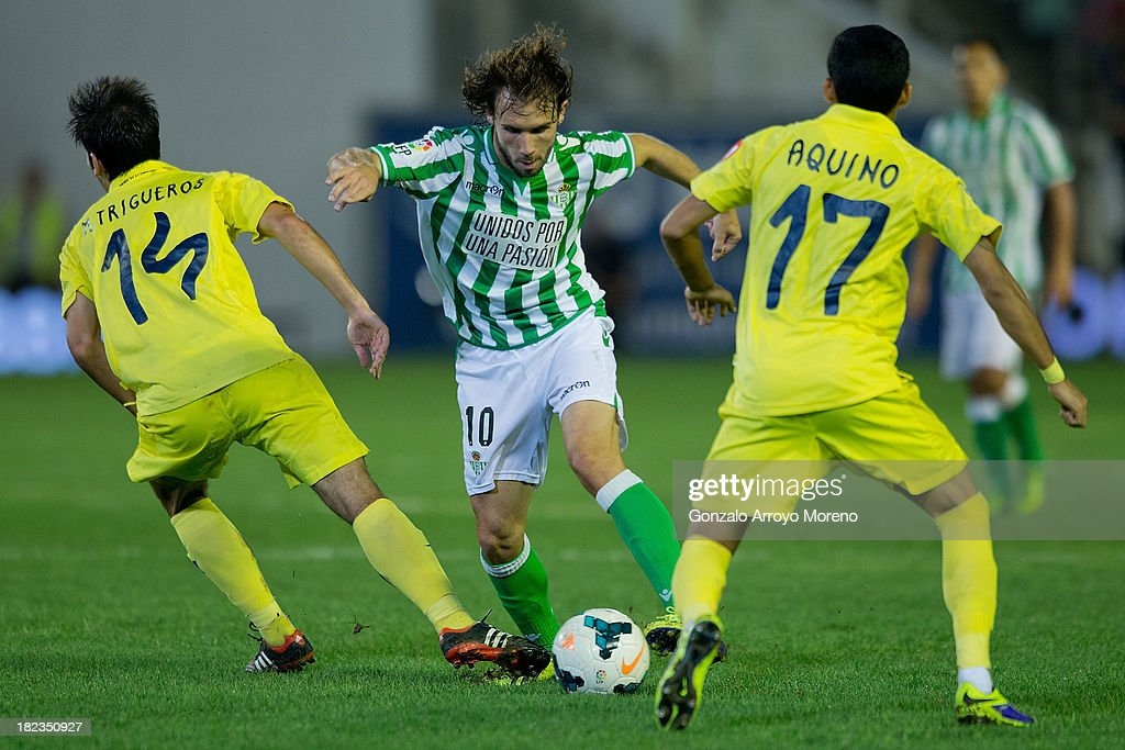 <a gi-track='captionPersonalityLinkClicked' href=/galleries/search?phrase=Joan+Verdu&family=editorial&specificpeople=3977903 ng-click='$event.stopPropagation()'>Joan Verdu</a> of Real Betis Balompie competes for the ball with Manuel Trigueros (L) and Javier Ignacio Aquino (R) of Villarreal CF during the La Liga match between Real Betis Balompie and Villarreal CF at Estadio Benito Villamarin on September 29, 2013 in Seville, Spain.