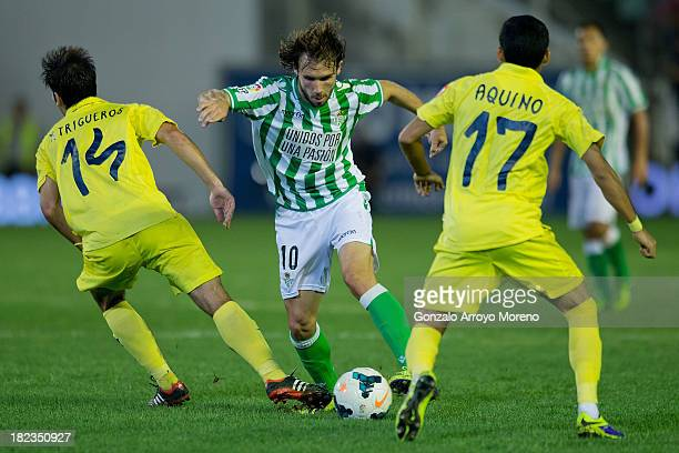 Joan Verdu of Real Betis Balompie competes for the ball with Manuel Trigueros and Javier Ignacio Aquino of Villarreal CF during the La Liga match...
