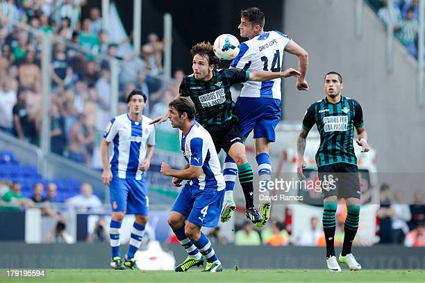 Joan Verdu of Real Betis Balompie duels for the ball with David Lopez and Victor Sanchez of RCD Espanyol during the La Liga match between RCD...