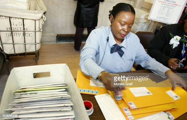 Joann McNeill a postal worker at the James A Farley post office places cancellation stamps on envelopes bound for the IRS as lastminute tax filers...